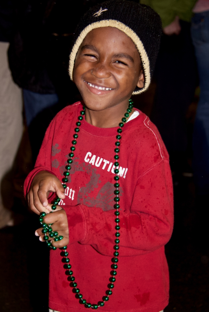 boy smiles for the camera at Mardi Gras parade laurie best photo